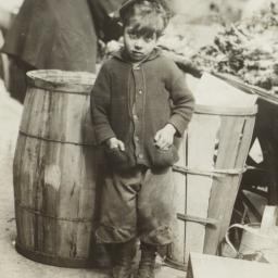 Boy near Barrels and Pushcart