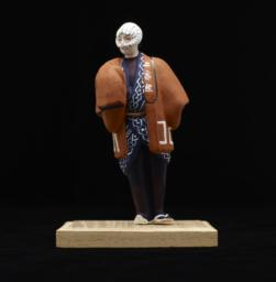 Figurine On Stand Of Male With Cloth Covering Face